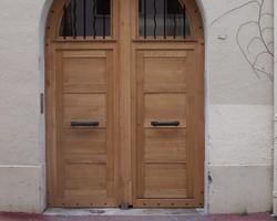 Porte cochère en chêne avec vitrages protégés par des barreaux métalliques