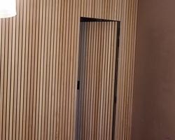 Cloison avec porte intégrée  Tasseaux frêne sur stratifié noir