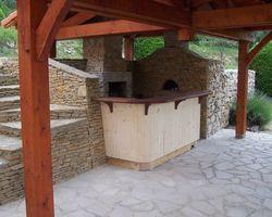 Cuisine d'été avec tablier cintré en épicéa et plan snack en sipo. Plan de travail et évier en pierre